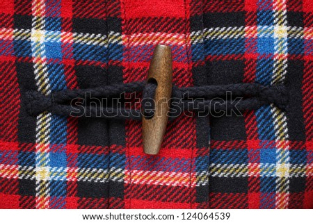 Close-up of button on checkered coat, for backgrounds or textures