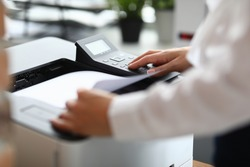 Close-up of cabinet worker using printer for working moment. Person in stylish white shirt. Device for office work. Man pressing button. Business and successful company concept