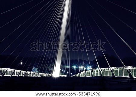 Close-up of cable-stayed bridge / suspension bridge illuminated in darkness. Modern urban architecture with night lighting. Fragment of luminous nocturnal hi-tech cityscape.  #535471996