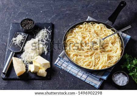close-up of cacio e pepe, spaghetti mixed with grated cheese and dusted with freshly ground black pepper in a skillet with a fork. ingredients on a black stone board, view from above Foto d'archivio ©