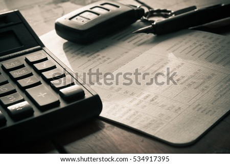 close up of calculator ,car remote and account book in finance and banking concept