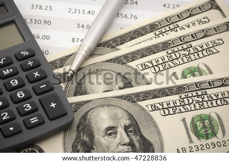 Close-up of calculator, pen and dollars on financial table.