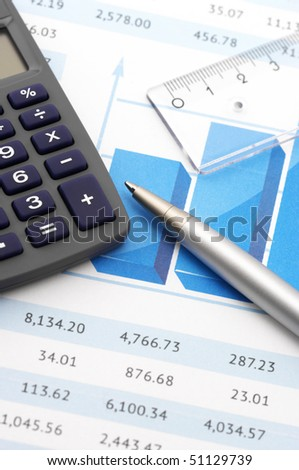 Close-up of calculator, pen and rule on paper table with graph.