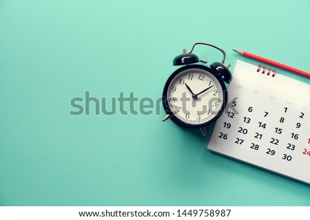 close up of calendar and alarm clock on the green background, planning for business meeting or travel planning concept