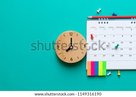 close up of calendar and clock on green background, planning for business meeting or travel planning concept