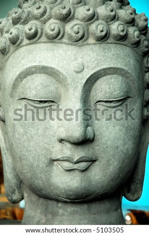 close up of calm face of a stone buddha statue