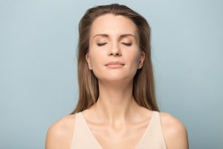 Close up of calm happy Caucasian millennial woman isolated on blue studio background relax with eyes closed meditate relieve negativity, peaceful young female breathe fresh air, stress free concept