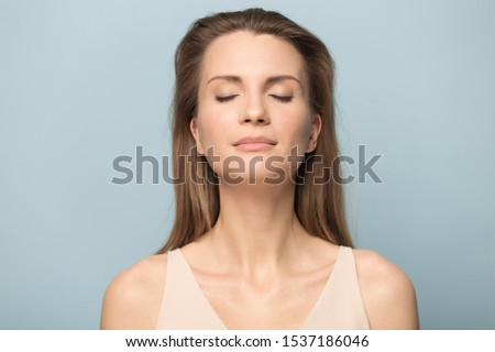 Close up of calm happy Caucasian millennial woman isolated on blue studio background relax with eyes closed meditate relieve negativity, peaceful young female breathe fresh air, stress free concept 商業照片 ©