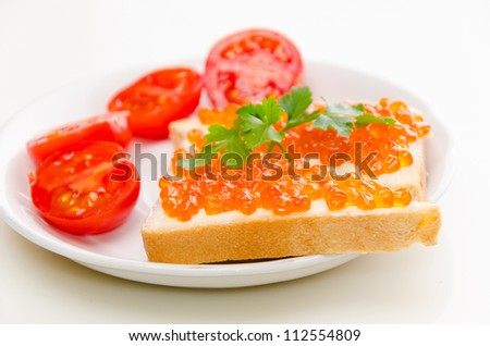 Close-up of canapes with butter and salmon caviar and cherry tomatoes on plate