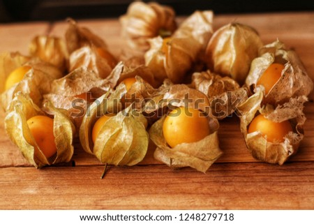 close up of cape gooseberry fruit on wooden background with dry calyx