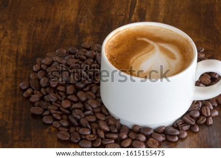Close up of cappuccino with frothy foam with latte art and coffee beans on black wooden table near the window with a light shade on the tabletop at cafe, white ceramic cups, coffee cup, Top view
