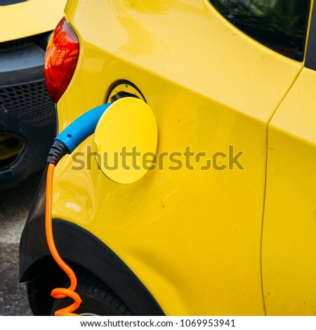 Close up of car being charged electronically at a public rechargeable dock station. #1069953941