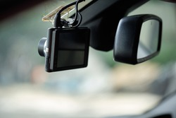 Close up of car camera mount on windshield. Car camcorder is onboard camera that records the view through a vehicle's front windscreen. Dashcams can provide video evidence in event of a road accident.