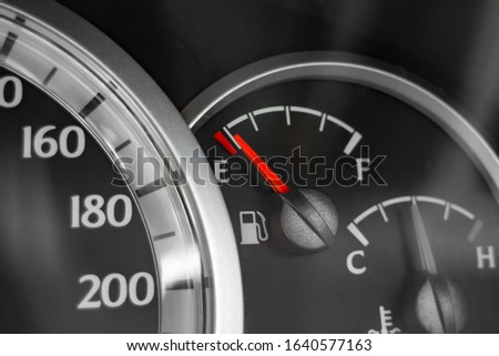 Close-up of car dashboard showing speedometer, fuel indicator and temperature indicator.