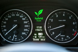 Close up of car dashboard with green hybrid mode icon on.