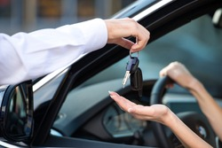 Close up of car dealer giving keys of a new car to woman. Concept for car rental