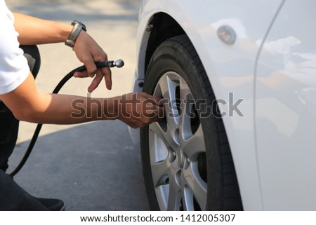Close-up of car mechanic working and pumping air into auto wheel in auto repair service #1412005307