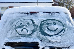 close up of car screen covered in snow with two emoji faces drawn into ice, one happy and one sad. outside on a cold sunny winter's day