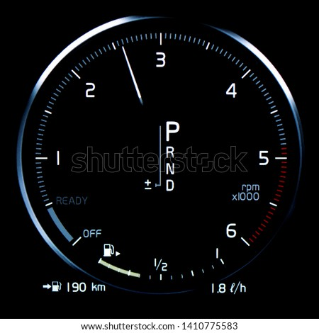 Close up of car tachometer displaying over 2500 RPM. Modern vehicle digital dashboard with driving range display, average fuel consumption and gear position indicator. #1410775583