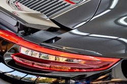 Close up of car taillight & aerodynamic design of modern luxury sportscar with reflection on black paint after wash & wax. Shiny supercar. Concept of car detailing and paint protection background