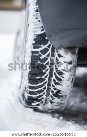 Close up of car tire covered with snow on a slippery road