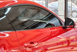 Close up of car window tint. Ceramic film provide heat rejection & UV protection with color stable shade. Automobile film installed to glass surface of red car. Professional tinting service background
