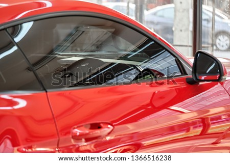 Close up of car window tint. Ceramic film provide heat rejection & UV protection with color stable shade. Automobile film installed to glass surface of red car. Professional tinting service background ストックフォト ©