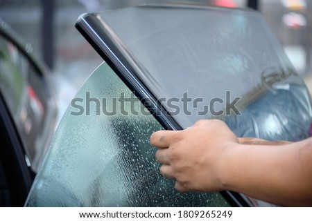 Close up of car window tint installation. Ceramic film provide heat rejection & UV protection. Automotive film installed to car glass surface. Professional tinting service background. Hand moving