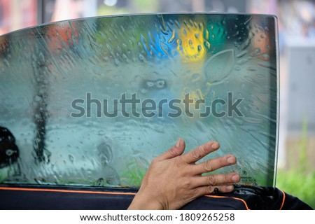 Close up of car window tint installation. Ceramic film provide heat rejection & UV protection. Automotive film installed to car glass surface. Professional tinting service background. Focus on hand.