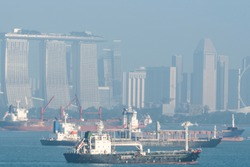 Close-up of cargo ships and buildings in the background on a cloudy morning in the port of the city of Singapore