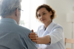 Close up of caring young Caucasian female nurse or caregiver touch support senior male patient, attentive woman doctor or GP feel supportive comfort upset mature man client, elderly healthcare concept