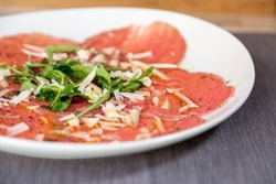 Close up of carpaccio meat with parmesan cheese and arugula in a white plate on a wooden table. With olive oil.