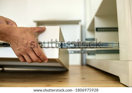 Close up of carpenter hands installing wooden drawer on sliding skids in contemporary cupboard cabinet. Stock photo ©