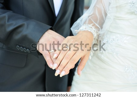 close-up of caucasian couple's hands with wedding rings