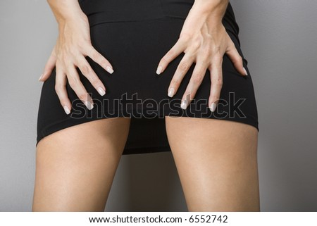 Close up of Caucasian female  wearing miniskirt with hands on buttocks. #6552742