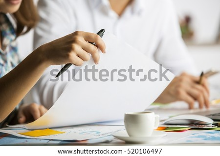 Close up of caucasian man and woman doing paperwork on messy table with coffee cup. Teamwork concept