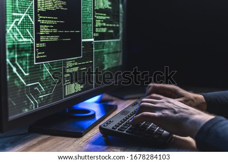Close-up of Caucasian man hands typing data on a keyboard,seen on a computer monitor
