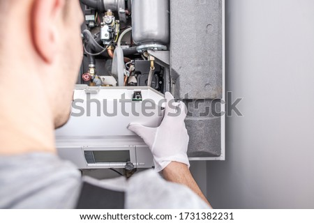 Close Up Of Caucasian Service Worker Fixing Central Heating Furnace System.  ストックフォト ©