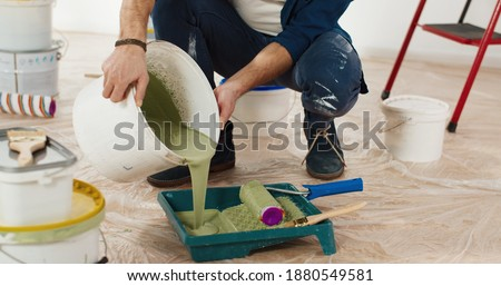 Close up of Caucasian young handsome man pouring green olive paint preparing for painting walls in house renovating and redesigning room. Handyman working on apartment redecoration repair and makeover Photo stock ©
