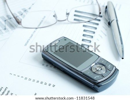 Close-up of cellphone with modern silver pen and reading glasses on top of potential growth charts and graphs. Blue tone image