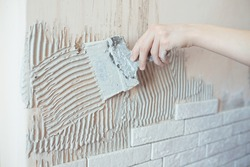 Close-up of ceramic tiles with glue on the wall, worker applies tile adhesive to the wall, make repairs in the apartment