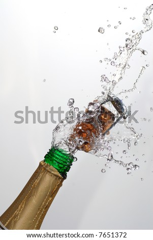 Close up of champagne cork popping with white background