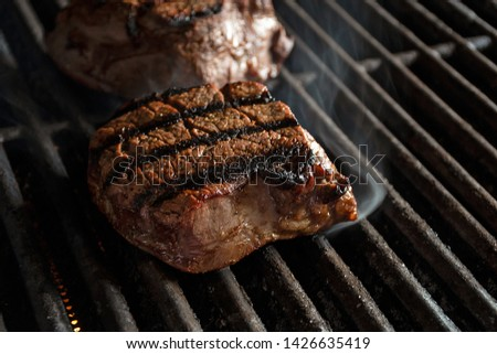 close up of charbroiled filet mignon beef on infrared barbecue grill