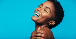 Close up of cheerful young woman with colorful makeup. Beauty portrait of female model with vivid makeup laughing on blue background.