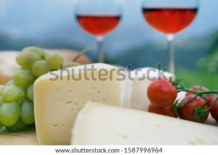 Close up of cheese, tomatoes, grapes and wine outdoors