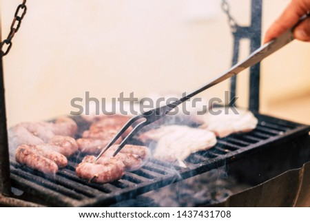 Close up of chef cooking meat on a warm grill - sausages on bbq - home nbarbecue to share dinner with friends in outdoor leisure activity for festiviy or holiday concept