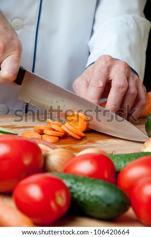Close-up of chef's hands chopping fresh carrot