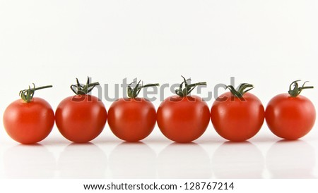 Close Up of cherry tomatoes on the vine .