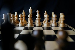 Close-up of chess on a black background. Wooden chess pieces. Concept: the Board game and the intellectual activities.