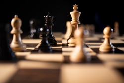 Close up of chess pieces on a chess board, representing strategy and tactics